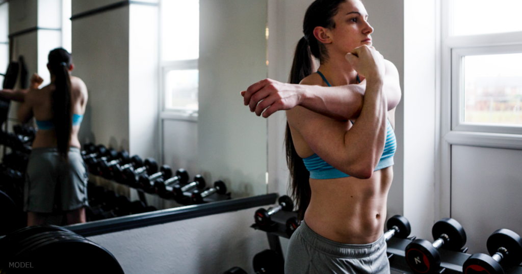 A woman stretches out her arm in a a weightroom.
